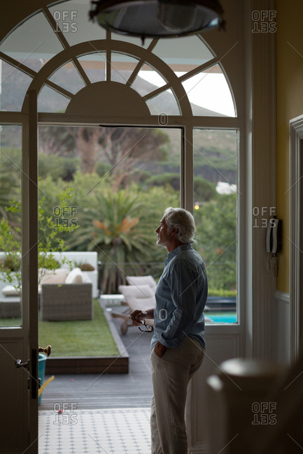Thoughtful senior man standing near door at home