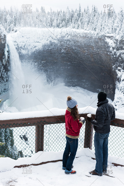 Couple in warm clothing looking at waterfall during winter