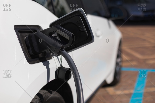 Close-up of electric car being charged at charging station