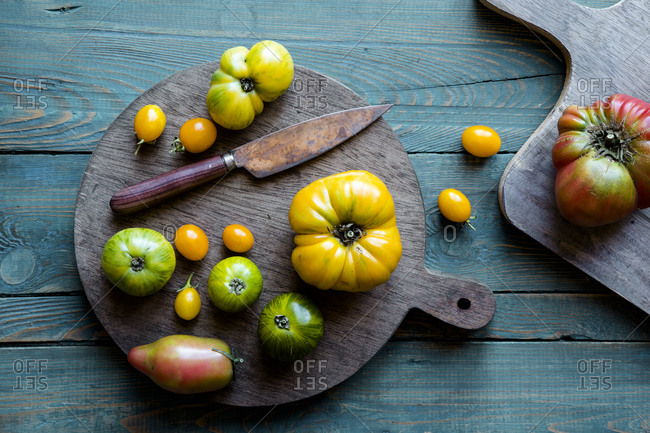 Green and yellow heirloom tomatoes on a cutting board