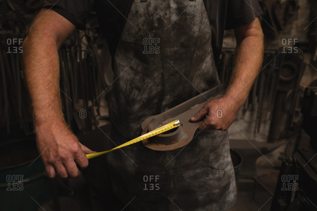 Blacksmith measuring a metal with measuring tape in workshop