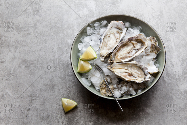 Oysters in a bowl of ice with fresh lime slices