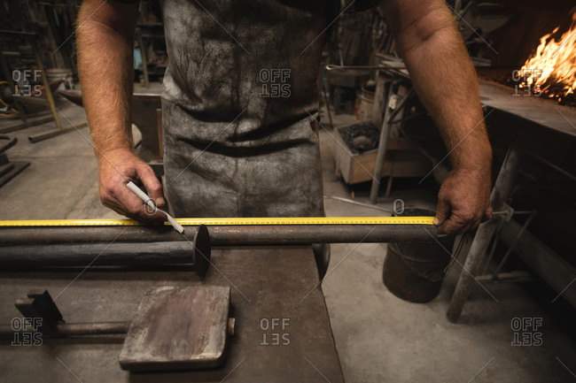 Metalsmith measuring a metal rod with measuring tape