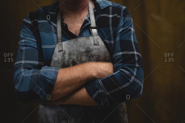 Mid section of blacksmith standing with arms crossed in workshop