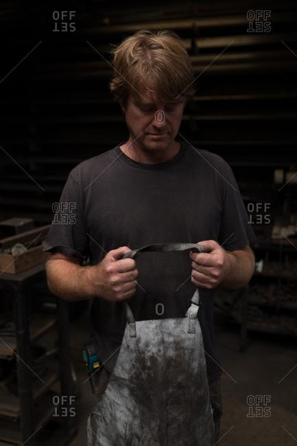 Thoughtful blacksmith wearing apron in workshop