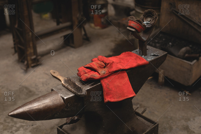 Hand wire brush and gloves on anvil in workshop