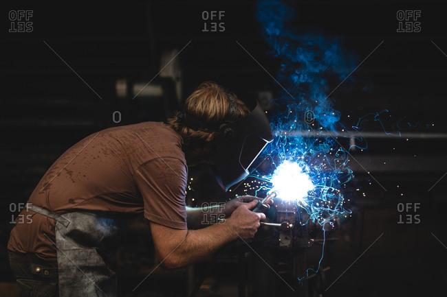 Blacksmith using a welding torch in workshop