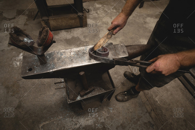 Blacksmith using hand wire brush on metal rod in workshop