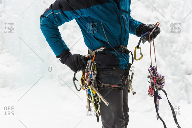 Mid section of male rock climber wearing harness near rocky mountain during winter