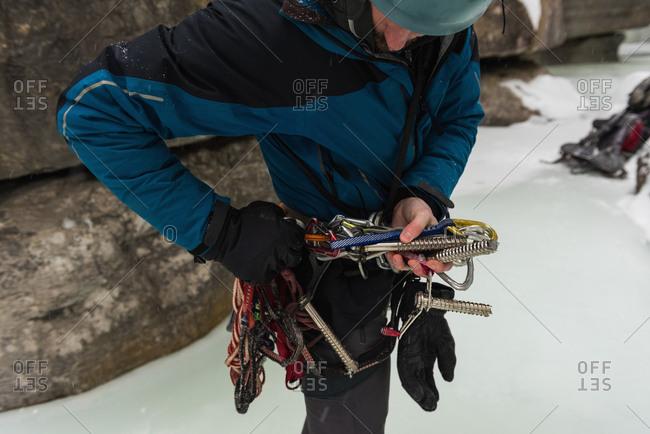 Male rock climber wearing harness near rocky mountain during winter