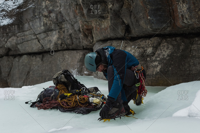 Male rock climber wearing crampons near rocky mountain during winter