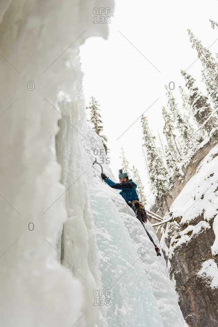 Male rock climber climbing ice mountain during winter