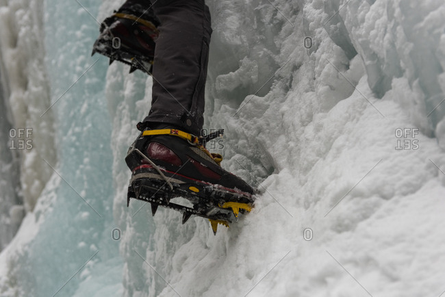 Low section of male rock climber climbing ice mountain