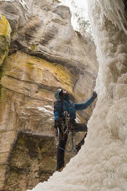 Male climber standing near rocky mountain during winter