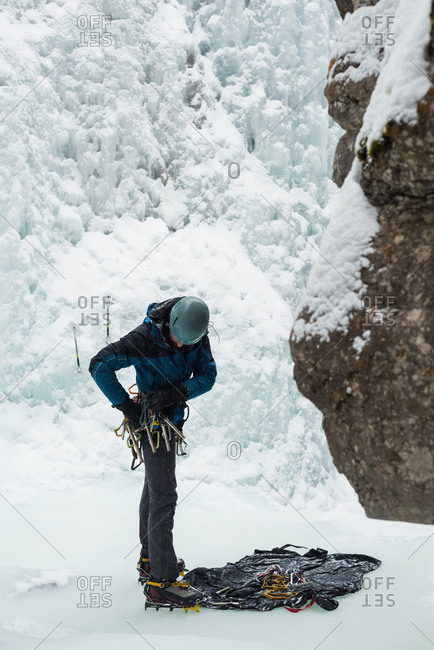 Male rock climber wearing harness near rocky mountain during winter