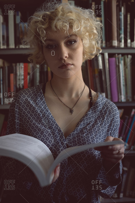 Portrait Of Young Woman Holding A Book In Library Stock