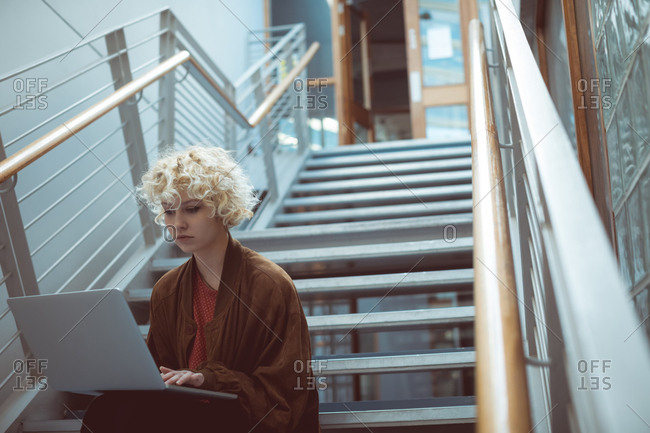 Young woman using laptop on staircase in library