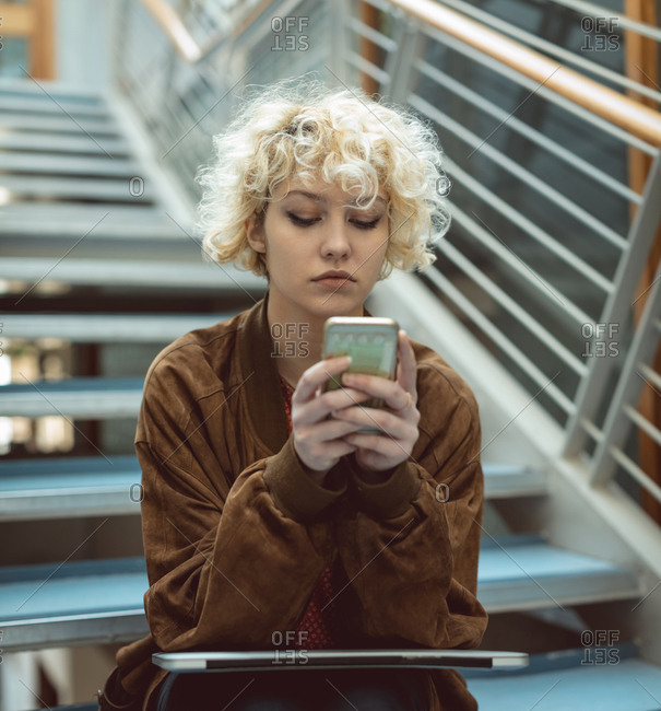 Young woman using mobile phone on staircase in library