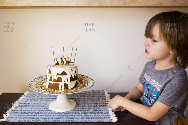 Little boy sitting at table looking at his birthday cake
