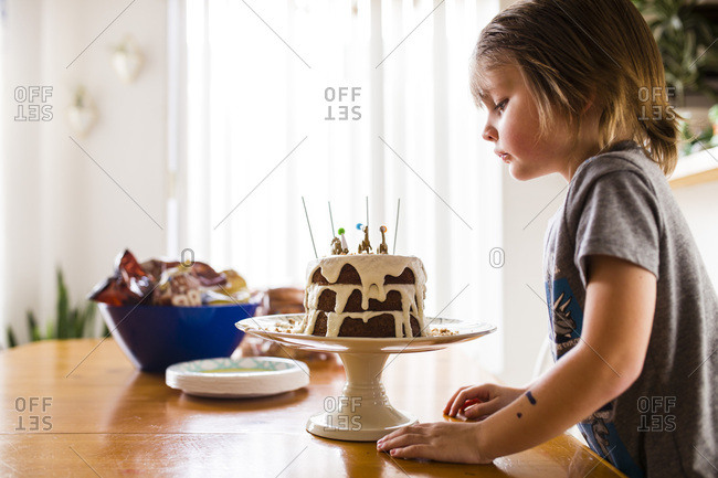 Little boy looking at his birthday cake