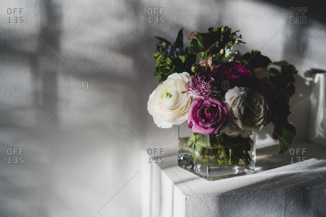 Purple and white flowers arranged in a square glass vase