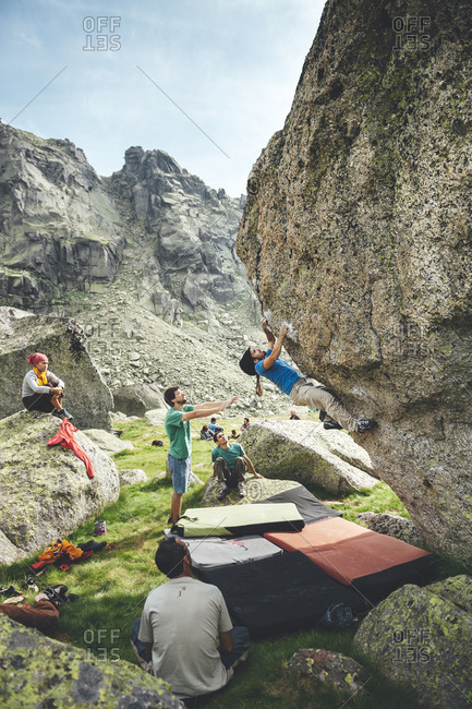 Hoya Moros, Spain - July 2, 2011: Rock climber practicing climbing on a granite overhang with crash pads and companion for safety