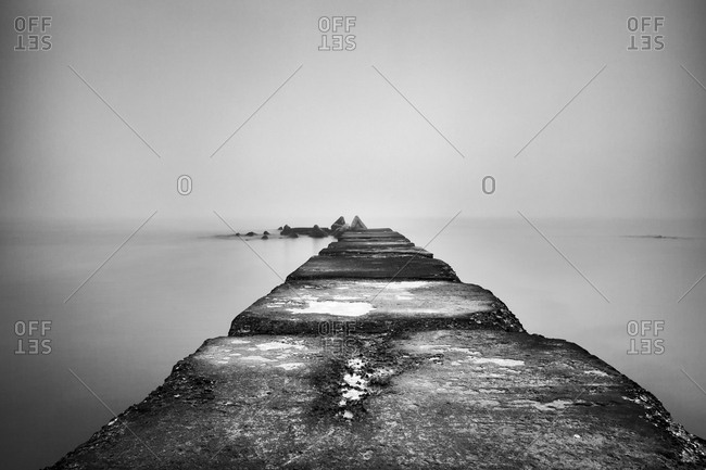 A pier on a sea shore in a foggy winter day, Port Balchik, Bulgaria