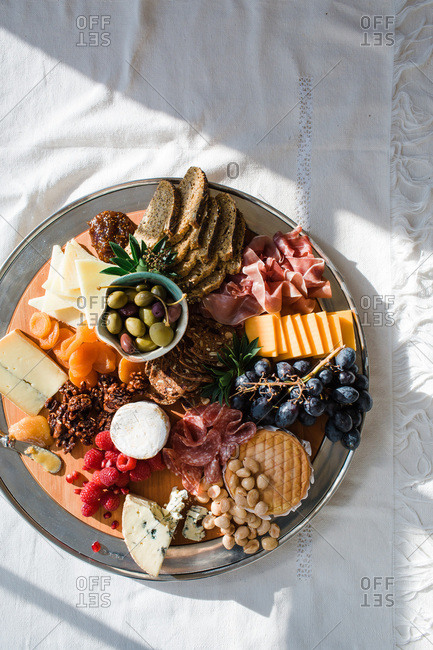 Circular tray of cured meats, cheeses, breads, and fruit on sunny dining table
