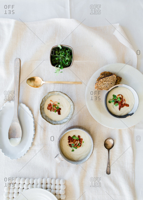 Three bowls of creamy soup among spoons and serving ware on table
