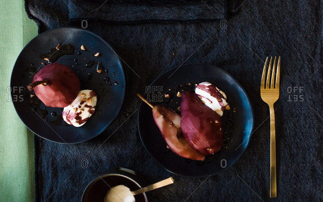 Two servings of poached pear in wine sauce on matching saucers and dark linen