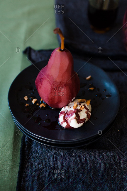 Full poached pear in red wine sauce with creamy topping and nuts