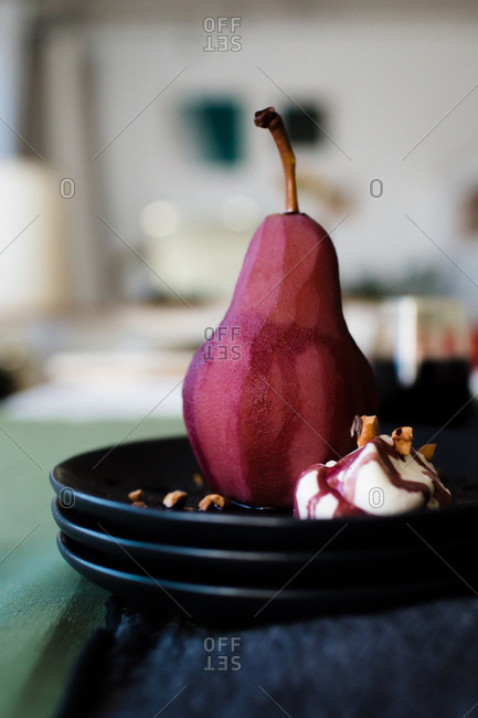 Side view of homemade pear desert poached in wine sauce