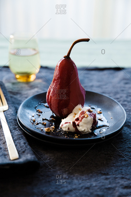 Lunchtime dessert at home with poached pear and wine sauce drizzle