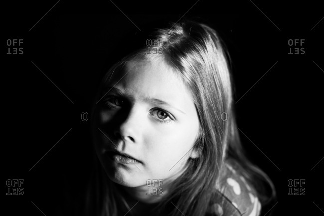 Serious portrait of young blonde girl in black and white