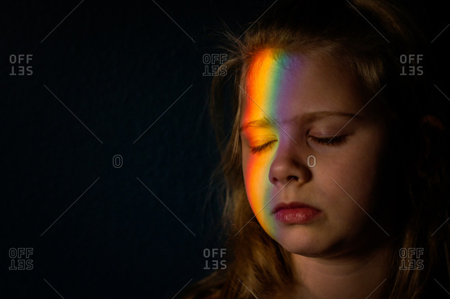 Prism reflection on young girl's face in the dark