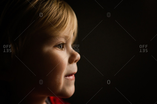 Side profile view of blonde toddler 's face against dark background