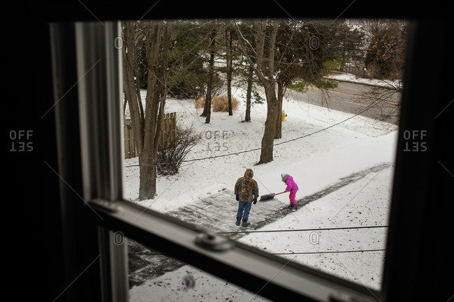 Upper floor view of father and daughter shoveling snow out of driveway