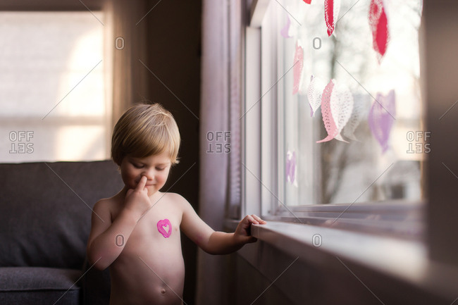 Mischievous toddler picking nose at window