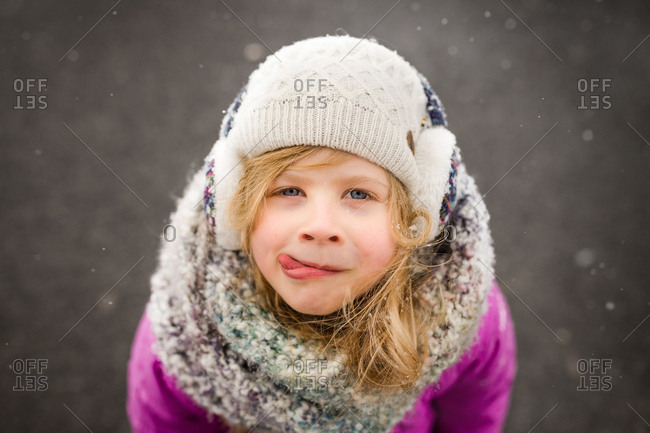 Blonde girl licking lips to taste fallen snow