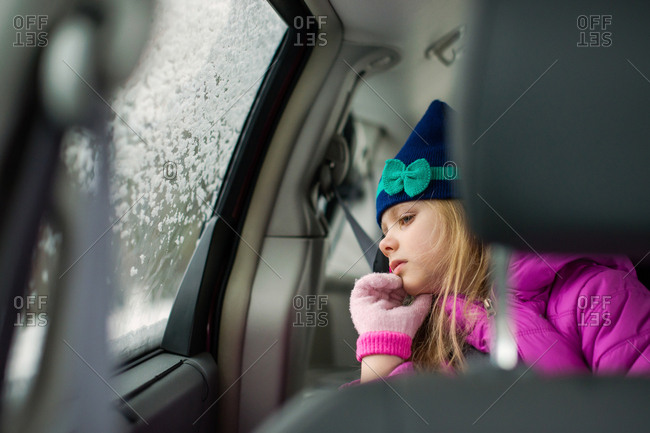 Girl passenger peering curiously out frosted car window