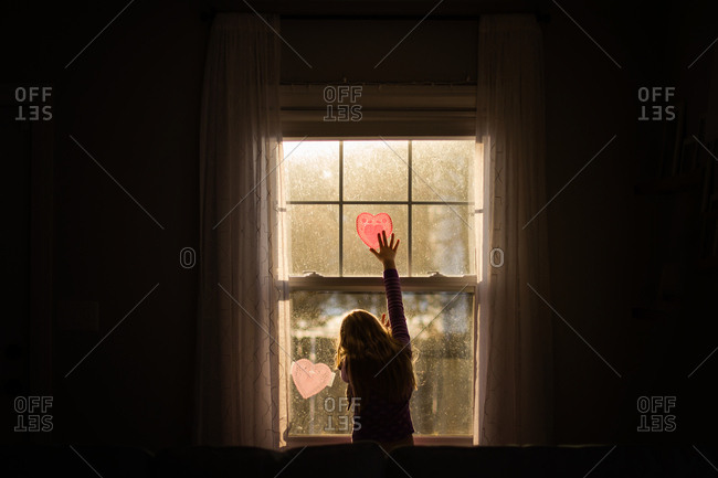 Girl reaching for Valentine decoration hanging in window