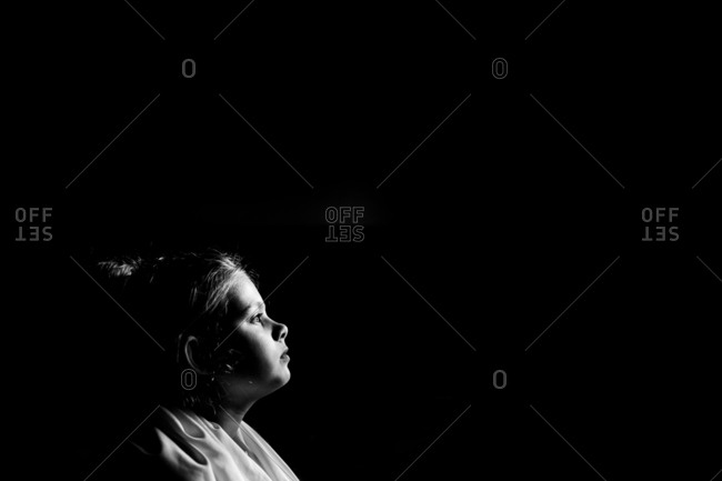Dramatic black and white portrait of little girl with sheet in dark room