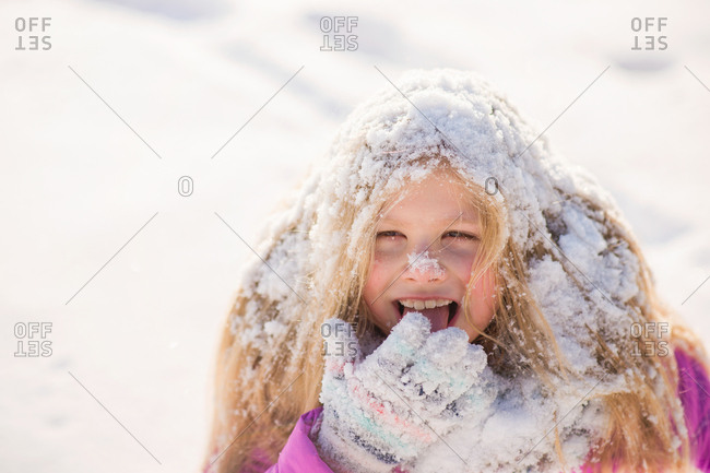 Girl covered in snow laughing outside