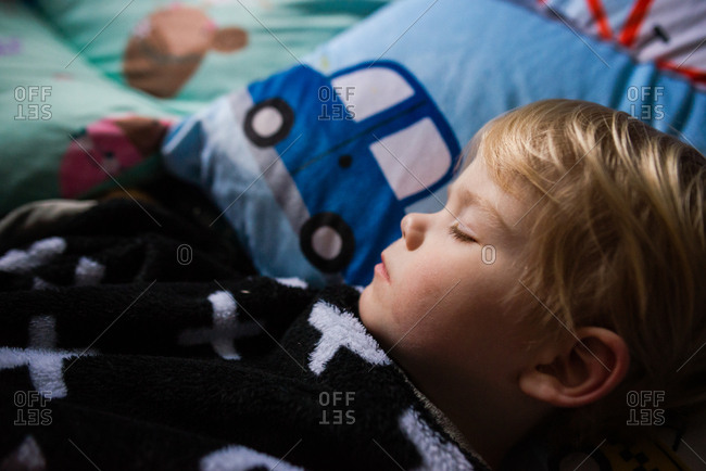 Toddler boy taking peaceful nap in bedroom