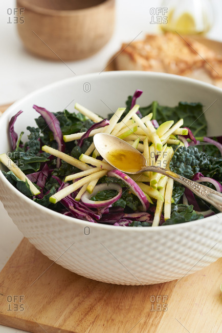 Kale and apple salad in mixing bowl