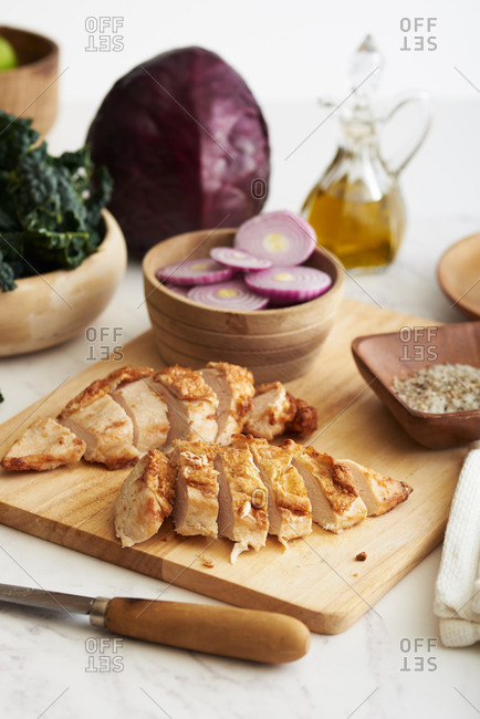 Grilled chicken breast slices on wooden cutting board