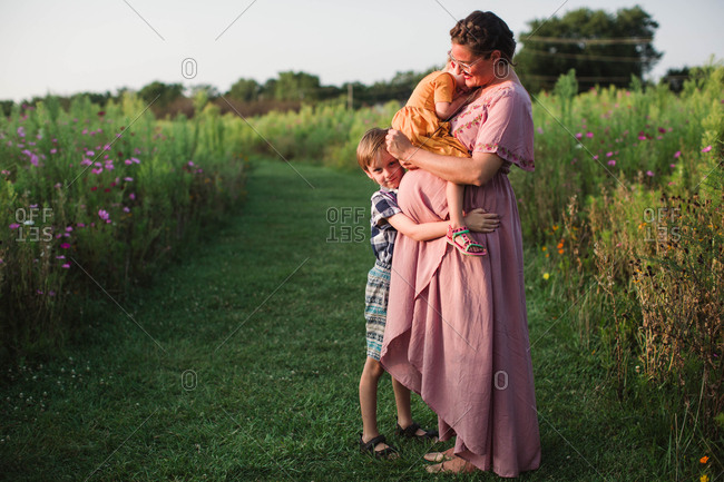Pregnant mother and her two children in a field at sunset