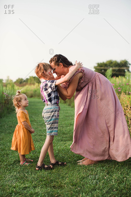 Pregnant mother gazing into her son's eyes in a field