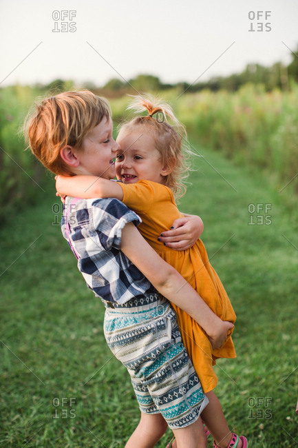 Boy carrying little sister in a field at sunset