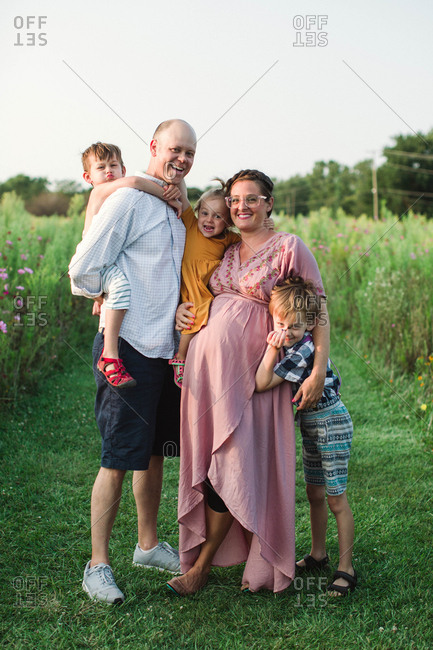 Happy family embraced and making silly faces in a field at sunset